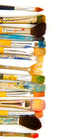 Used paint brushes stained a range of colours lined up vertically.