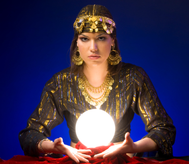 A woman dressed like a gypsy fortune tellerwith gold jewellery and a glowing crystal ball
