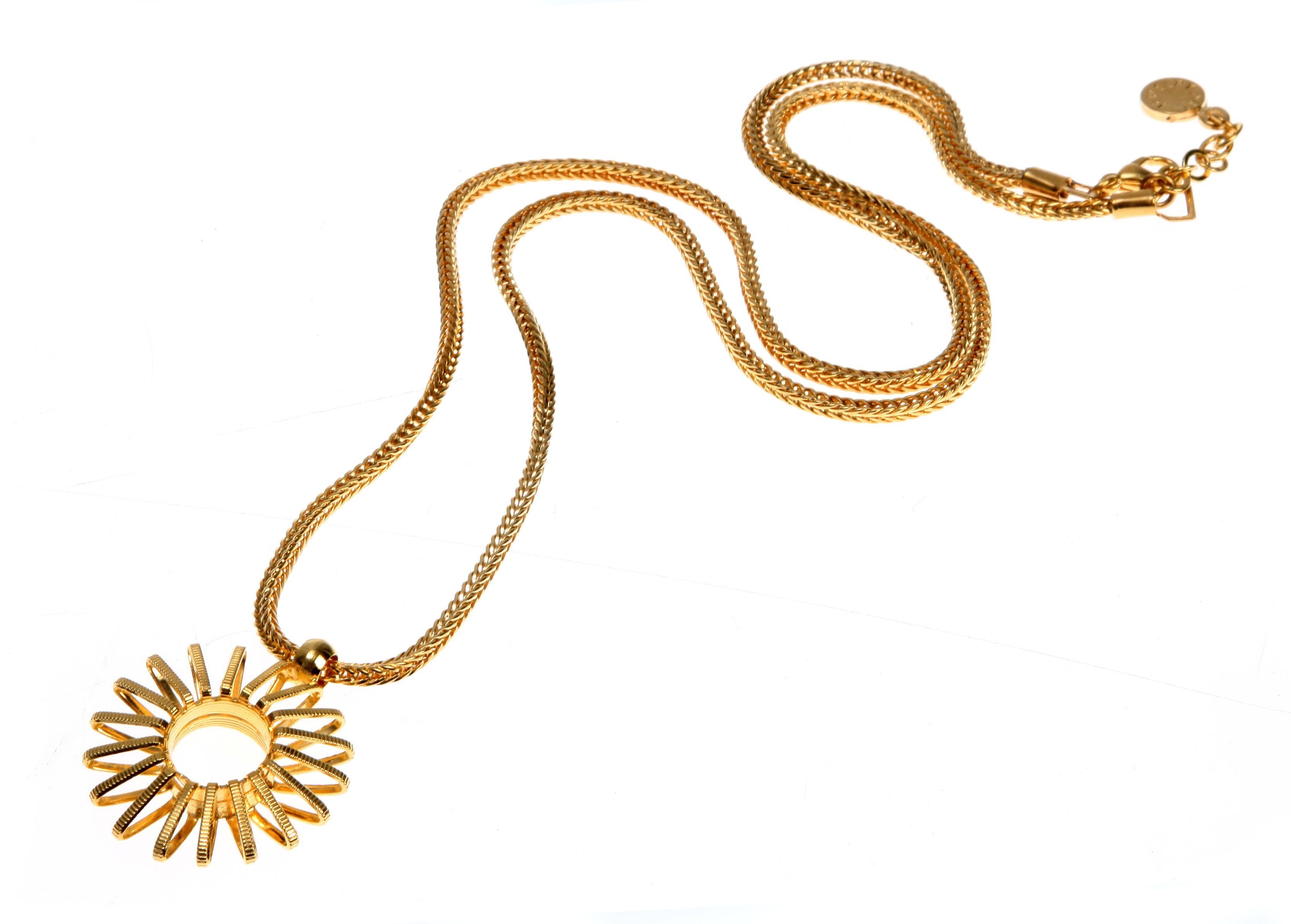 A gold sun charm on a gold chain on a white background
