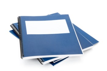 A pile of blue spiral bound notebooks